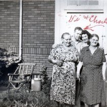 Image of 9126 South 54th Avenue - This is a photograph featuring a view of the back entrance of the home located at 9126 S. 54th Avenue. From l-r: Ana Bakutis (mother of Charles Bakutis); Charles Bakutis; his wife, Viola Bakutis; and Viola's mother, Kate Guersch. Just to the right of the group, the door to the cellar of the home is visible. The home was purchased by Viola and Charles Bakutis in 1953. Today it is known as the Chapman House (Harker Farm House), a historical landmark that was built in 1924. The home was built on vertical poles and had no foundation. There was a cellar in the rear of the house that contained a coal burning furnace and coal bin. Bakutis later put in a foundation and enlarged the cellar.