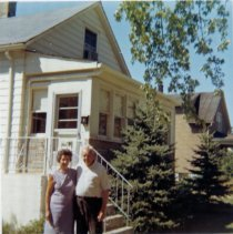 Image of 9126 South 54th Avenue - This is a photograph featuring Viola and Charles Bakutis standing in front of their home located at 9126 South 54th Avenue. The home was purchased by the Bakutis family in 1953. Today it is known as the Chapman House (Harker Farm House), a historical landmark that was built in 1924. The home was built on vertical poles and had no foundation. There was a cellar in the rear of the house that contained a coal burning furnace and coal bin. Bakutis later put in a foundation and enlarged the cellar. In this photograph, the home has been updated on the exterior with aluminum siding.