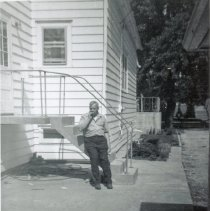 Image of 9126 South 54th Avenue - This is a photograph Charles Bakutis sitting on the back stairs of the home located at 9126 South 54th Avenue. The view is looking west from the back of the home to the east. The home was purchased by the Bakutis family in 1953. Today it is known as the Chapman House (Harker Farm House), a historical landmark that was built in 1924. The home was built on vertical poles and had no foundation. There was a cellar in the rear of the house that contained a coal burning furnace and coal bin. Bakutis later put in a foundation and enlarged the cellar. In this photograph, the home has been updated on the exterior with aluminum siding.
