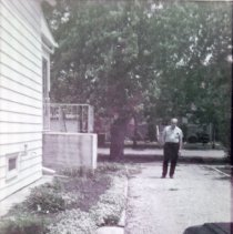 Image of 9126 South 54th Avenue - This is a photograph Charles Bakutis standing in the driveway of the home located at 9126 South 54th Avenue. The view is looking west from the back of the home to the east down the south facade of the home which is on the left. The home was purchased by the Bakutis family in 1953. Today it is known as the Chapman House (Harker Farm House), a historical landmark that was built in 1924. The home was built on vertical poles and had no foundation. There was a cellar in the rear of the house that contained a coal burning furnace and coal bin. Bakutis later put in a foundation and enlarged the cellar. In this photograph, the home has been updated on the exterior with aluminum siding. A pipe for receiving heating oil can be seen on the side of house near a small window.