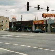 Image of 5100 Block of 95th Street - This is a photograph of the intersection of 5100 block of 95th Street in 1996. This view is from the northwest corner of the intersection of 95th Street and 52nd Avenue looking to the southeast. Businesses along 95th Street, left to right, include the Oak Lawn Car Wash, at 5101 W. 95th Street, the Brandt Building, located at 5131 W. 95th Street, which housed Brandt's Tavern and Super Burrito, The Safeman, located at 5163 West 95th Street, Ready-To-Finish Furniture, located at 5165 West 95th Street, Remax One Inc., located at 5167 West 95th Street, are visible. All of these buildings have since been demolished and replaced by the Harris Bank Commercial District. The stoplights at the intersection of 95th Street and 52nd Avenue are in the foreground of the photograph. Just barely visible in the left  is the sign for Ricketti's Ristorante located at 5172 West 95th Street, on the northeast corner of the intersection.