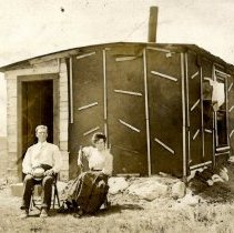 Image of Unknown man and woman & tar paper house-postcard