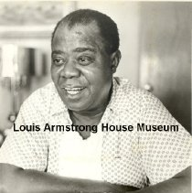 Image of Publicity photo of Louis Armstrong in his den.  Photo by Jack Bradley