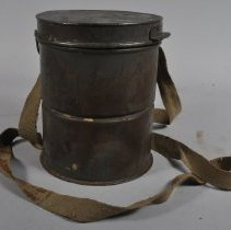 Image of Side view of canister-style carrying case and its strap
