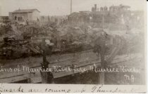 """Image of Postcard - This postcard appears to be a copy of a photo or postcard showing the charred remains of structure(s) in the community of Maurice River. Railroad locomotive in background. Notation on face of postcard reads """"(Ru)ins of Maurice River fire, Maurice River, N.J."""" Second line reads """"Guards are coming up Thursday eve""""."""
