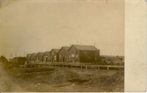 """Image of Postcard - B & W image of one and a half and two storie buildings, gable ends facing loading dock and rail siding. Sign on end of building nearest to camera reads in part """"Oysters"""". Location may be Maurice River, NJ."""