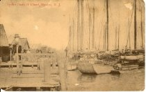 "Image of Postcard - Front depicts oysters schooners, scows, garveys docked.  Inscription printed in red ink:  Oyster Boats at Wharf, Bivalve, N.J.  Reverse of card has handwritten inscription in pencil:  ""From Bessie, Perry Emma can you get me a jobe up therr, by by"".  Addressed to Mrs. Emma Whelden, 427 South Second St., Millville, N.J. dated Jun 17, 1916"
