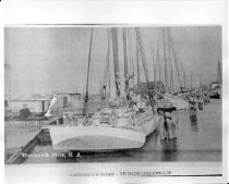 "Image of Print, Photograph - B & W digital copy of schooners tied up between shoreline and pilings.  ""Greenwich Piers-Ye Olde Greenwich"" printed at bottom of photograph. Yawl boat hangs off stern of nearest vessel."