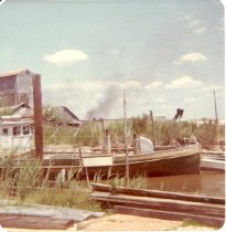 Image of Print, Photographic - Oyster boat with pilothouse docked at pilings.  Middleground shows two story shell crushing structure. Background shows smoke from marsh fire. Color, c.1970's