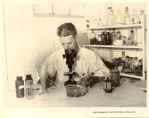 """Image of Print, Photographic - Laboratory  personnel examining sample under microscope.  Reverse side reads in pencil """"Biologist making microscopic examination of samples obtained in the oyster fields"""" and labeled in upper right corner """"OI-2-N"""" and in ink """"7232"""".  Printed pink label reads """"from Graphic Features, The McAlpin, Broadway at thirty-fourth, New York City."""" See 2005.15.07 for duplicate."""