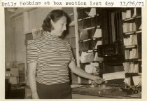 Image of Print, Photograph - B & w digital image of women (picture labeled Emily Robbins) standing on service side of postal boxes on the last day of operation for the Bivalve Post Office.