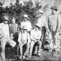 """Image of Early Pioneers (7 men) - Photo of George Granger, Willis Guearo, Edward Cox, Wallice Woodbury, Mat Reese, William Abbott, James E. Hughes, working at Lead Mine on Bunkerville Mountain owned by Zilpha Hughes in the mountains southeast of the valley in 1916. Though it was a rich vein it turned out to be too costly to mine and haul out."""" Images of America Mesquite and the Virgin Valley"""" by Geraldine White Zarate"""