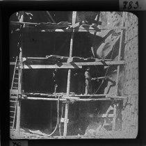 """Image of """"Fremstilling af vandtæt Puds paa Dæmningsmuren i Kraftværket """"Amsteg"""", Schweiz, ved hjælp af Mørtelsprøjte.""""  Således beskrevet i protokol over diassamling anvendt i undervisningen på bygningsfagene under overskriften: """"Billeder vedrørende Mørtelsprøjte skænkede af Nienstædt og Co.""""   Med dias som dette blev danske broingeniørstuderende op gennem det 20. århundrede undervist af samtidens markante professorer i brobygning.     Samlingen giver indblik i omfanget af viden, de studerende skulle tilegne sig i løbet af studieårene på læreanstalten. Ikke kun konstruktion og materialeforståelse, men også evnen til at se på helheden – broen i landskabet – var centralt i undervisningen og var medvirkende til at gøre danske broingeniører internationalt eftertragtede."""