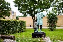 """Image of Kunstner: August Vilhelm Saabye (1823-1916) Bronzefigur/portræt af Julius Thomsen Indviet d. 20. februar 1906 i Sølvgade.   Om værket: Udenfor Institut for Byggeri & Anlæg, ved bygning 118, står en lille bronzefigur med en stor historie. Oprindeligt blev bronzestatuetten skabt til DTU's gamle lokaler i Sølvgade, hvor den blev afsløret d. 20. februar 1906 i anledning af J. Thomsens 80 års fødselsdag. Det er netop J. Thomsen (Hans Peter Jörgen Julius Thomsen), professor i kemi og direktør ved Den Polytekniske Læreanstalt i årene 1883-1902, der er statuens motiv. Bronzefiguren viser os en af landets førende og mest indflydelsesrige videnskabsmænd. I 1853 udtog Julius Thomsen patent på en metode til fabrikation af soda af mineralet kryolit, og i 1856 blev han direktør for fabrikken Øresund, der anvendte kryolit til produktion af soda efter Julius Thomsens metoder (det formodes at statuen står i et bed med kryolitsten).  Fra 1864 underviste Julius Thomsen på Københavns Universitet i kemi, og fra 1866 var han fastansat professor i kemi og bestyrer af universitetets laboratorium. Som rektor for Den Polytekniske Læreanstalt fra 1883 gennemførte han væsentlige reformer i undervisningen og stod for opførelsen af Læreanstaltens nye bygninger på Sølvtorvet i København. Internationalt blev Thomsen kendt for sine termokemiske undersøgelser - han var den første som bevidst anvendte loven om energiens konstans som grundprincip for termokemien.  Thomsen """" var hverken inspirerende, åndrig eller intellektuel"""", men han var en meget dygtig eksperimentator, """"arbejdsom, produktiv og skarpsindig"""" (citeret af Nielsen., A.K. i Kjærgaard, 2005, s. 131). Kilder: DTU Historie - og samlingsdatabase & www.historie.dtu.dk Om kunstneren: August Vilhelm Saabye var en dansk billedhugger. Oprindelig blev han uddannet håndværker, men havde et ønske om at udvikle sig yderligere gennem kunstakademiet hvor han blev optaget i 1842. En række konkurrencer skabte opmærksomhed omkring A. Vilhelm og i """