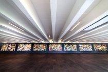 """Image of Kunstner: Lars Nørgård (f. 1956) Titel: Syv magiske muldvarper/ Seven Magic Moles, udført i 2010.  Skænket af Ny Carlsberg Fondet i 2011. 7 malerier af 165 x 350 cm - samlet 28 meter langt værk. Olie og akryl på lærred.  Om værket: De syv magiske muldvarper af Lars Nørgård har en af de mest centrale placeringer på DTU i Lyngby og er desuden et af de nyeste værker i universitetets samling. Værkerne hænger farvestrålende i en af de to store vandrehaller, som er 15 meter bred og 100 meter lang. De to vandrehaller ligger på hver sin side af Grønnegården og kaldes til dagligt for landingsbanerne. Navnet peger tilbage til stedets tidligere funktion som Lundtofte flyveplads fra 1917-59, hvor flyene lettede og landede hvor universitetet i dag er placeret. Værkerne af Lars Nørgård blev produceret gennem 2010 i kunstnerens atalier. Han tog cirka en måned om at male hvert værk. DTU's daværende rektor Lars Pallesen udtrykte stor glæde ved præsentationen af de syv malerier i 2011: """"Selvom vi er teknologer, teknokrater og nogle vil kalde os nørder, så er vores sans for værdisættelse af kunst, ikke mindre af den grund. Og vi er meget taknemmelige for, at Ny Carlsberg Fondet vil betænke os på denne her måde. Hjertelig tak."""" Med værkernes centrale placering har de fleste med en dagligdag på DTU nok på et eller andet tidspunkt passeret forbi den lange stribe af værker, som breder sig ud over 28 meters længde. Landingsbanen er en """"hovedvej"""" på universitetet, som skærer igennem hele bygning 101. Det er blandt andet her hvor hundredvis af studerende ligger i kø og holder """"ventefest"""", inden de kan købe de populære billetter til en af de største begivenheder på DTU, Årsfesten. Værket er en naturlig del af både hverdag og fest på skolen og sådan skal det forblive med at være.  For Lars Nørgård har værkerne en central opgave, nemlig at skabe glæde blandt de forbipasserende og selvom værkerne overordnede synes abstrakte, ser kunstneren selv noget figurativt kravle frem i overfladen:"""