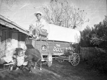Image of Doll House. 1950. George Strebe in a covered wagon pulled by cattle. Logo for the Doll House.  1032 North Palm Canyon Drive owners George and Ethel Strebe                                                                                                                                                                                       - 90-1491