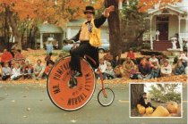 Image of Mr. Pumpkin rides his high-wheeler bicycle in parade