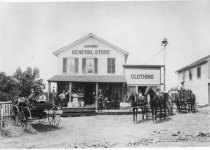 Image of A general store with customers, carriages and horses in the front - Photograph, Black-and-White