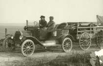Image of An old car hauling a wagon with hogs - Photograph, Black-and-White