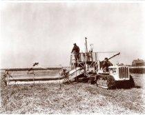 Image of Caterpillar Tractor pulling a grain binder harvesting a farm crop