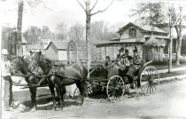 Image of Carriage with a man near two horses and four passengers in carriage - Photograph