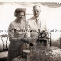 Image of Mary and Ed Smith cutting a cake. - Mary and Ed Smith cutting a celebratory cake.