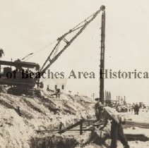Image of Building the bulkhead - Ponte Vedra Beach, Florida Crew with crane building sea wall Photo labeled on back -- Shore - line Builders, Jacksonville, FL