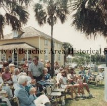 """Image of Mayport Railway Terminal Museum- Centennial Celebration- """"Sat. in the Park."""" - Jacksonville Beach, Florida  Saturday, April 28,1984  Centennial Celebration, """"Saturday  in the Park"""", dedication of Mayport Railway Terminal Museum, Pablo Historic Park.   (Standing): Mr. Harry G. Dow. Crowd seated in park.  (Mrs. Robert) Ruth O'Neill at podium."""