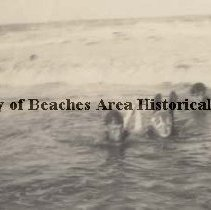 Image of People laying on stomachs in the water with waves washing over them. - Pablo Beach, Florida 