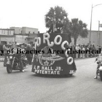 Image of Parade Float for Morocco Shrine - Jacksonville Beach, Florida Parade down 2ND Street, North. Morocco Float with J.P. Hall, Jr., Potentate. Cinotti's bakery in background. ca. 1970