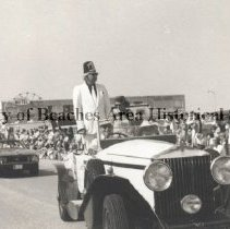Image of Welcome Day Parade - Jacksonville Beach, Florida. Welcome Day Parade on First St North.Guy Craig in Shrine outfit.Ferris wheel,Sundeck Motel (224 N.Ocean Front)Sea Shell Craft store,bathhouse in background. April 16,1972 Sunday