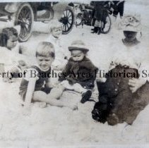 Image of Mrs. Corrie W. and son Frank W. sitting in the sand. - Pablo Beach March, 1917 .  Submitted by Mrs. Corrie W. (LeRoy , Sr.)  Bowers of Atlantic Beach.  Left to Right: Her son, Frank Bowers, now retired, living in Atlanta, GA.; her husband and older son Kelly , both deceased.   Other unidentified  children playing in sand in photo.      One of the family's monthly train trips from Springfield- Jacksonville, Fla. to what  was then Pablo Beach.Corrie W. ( LeRoy Bowers, Sr). with Frank W. and LeRoy Bowers Jr., sitting  in the sand.