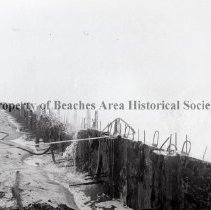 Image of Construction of the B.B. McCormick & Sons Seawall - Jacksonville Beach, Florida  Construction of the B.B. McCormick & Sons seawall (King pile) between 12th Ave.N and 13th Ave.N.  Surf splashing over partially constructed wall.