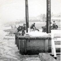 Image of Piling Sandbags at Atlantic Boulevard Ramp for Hurricane Cleo, 1964 - Neptune Beach, Florida Life guards piling sandbags at Atlantic Boulevard ramp before Hurricane Cleo, August 1964