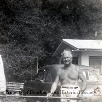 Image of Young woman in pleated skirt at waterside - Jacksonville Beach, Florida One of collection from A. G. Penman photos. This shows Penman in shorts in front of parked car holding end of stick with a quantity of small fish suspended from it. Cottage and trees in background.