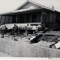 Image of Hurricane Dora 1964; Damage to Neptune Beach houses - Hurricane Dora; September 1964;another view of previous photo showing  damage to one-story house;  front porch undermined; men placing  temporary supports ; missing siding; missing  porch roof shingles, behind sea wall.