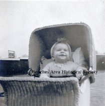 Image of Allen Pritchard -   Allen Pritchard in cap and sweater in wicker baby buggy with hood