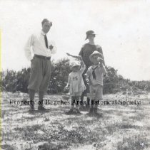 """Image of The Pritchards at Easter - George Pritchard  in shirt, tie and knickers with Pat and Allen, in """"sailor""""middy; both children in hats, holding Easter baskets. Mrs. Belt behind them. Scrub and ocean behind them."""