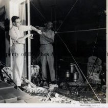 Image of Preparing for Hurricane - Man taping a large plate-glass window in a sporting-goods store.