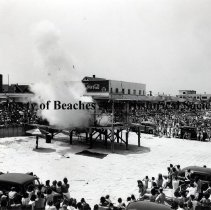 Image of Celebration and Explosion Performance at the Beach - Jacksonville Beach Boardwalk Huge crowd with cars at the beach surrounding large open space with cage-like structure on elevated platform. Something in the cage has exploded. There is a great white puff of smoke with debris flying. Some onlookers are holding their ears. Boardwalk and buildings in background.
