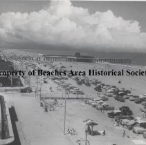 Image of Coaster Bath House & Band Shell - Jacksonville Beach,  Florida Beach scene showing Coaster Bath House and Band Shell  (left) at Ocean ramp and Pablo  Avenue; with cars on beach and pier in background. (two pictures - other  Accessn# 80-13-81)