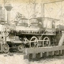 Image of Locomotive - Locomotive on tracks with engineer and 2 other workers.  Location unknown.