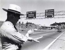 """Image of Beltway - Beltway (495) and 270 junction. Sentinel 14 Sept. 1967.  caption in Sentinel for photo: referring to short article, """"Two Killed in Mishap on Beltway"""" - """"Sgt Major Joseph D. Kavanagh of the State Police demonstrates what is happening all too often on Rt. 270 near the Beltway Overpass, which is visible in the rear of the photo.  Careless drivers fail to heed the directional signs farther back along the road and attempt last ditch multiple lane changes - with disastrous results."""""""
