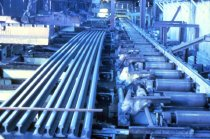 Image of Set of steel rails next to a set of steel rollers.