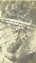 Image of Unidentified woman on tree trunk.