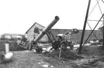 Image of Ford backhoe lifting new pipe 1963 (.031)
