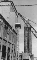 Image of Hoistiing new equipment to top of building 1960 (.037)