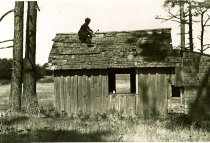 Image of Betty A. Lowman repairing chicken coop to live in.