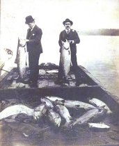 Image of Two men in suits with fish.