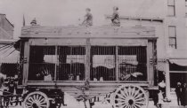 Image of D.IV.108 - Circus wagon passing Vendome Hotel
